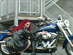 Red-haired biker in exciting striptease